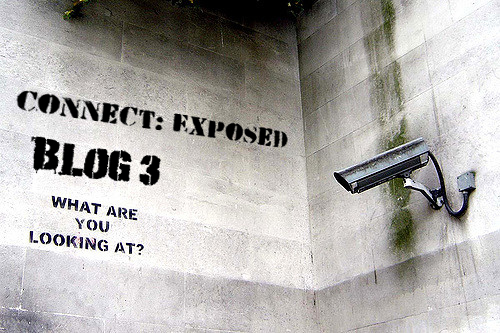 "A wall features a security and the text: ""Connect: Exposed, Blog 3, What are you looking at?"" in spray painted stencil."
